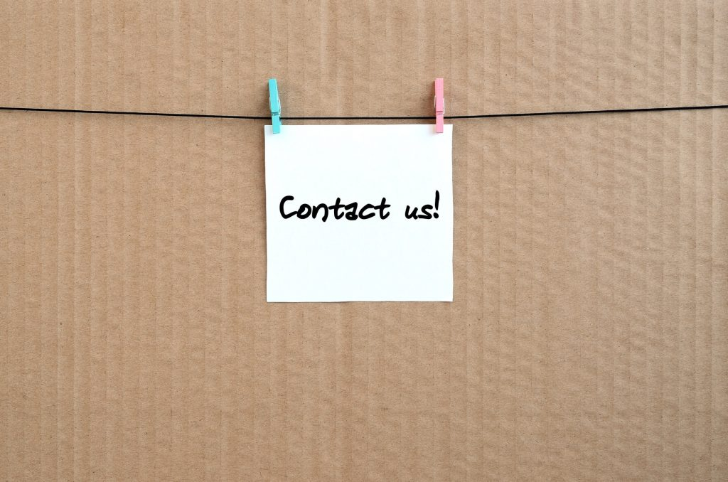 Contact us! Note is written on a white sticker that hangs with a clothespin on a rope on a